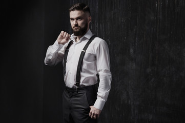 Attractive bearded man in a white shirt and suspenders standing near dark wall. He is strong, courageous and serious. He holds the collar of his shirt. Dark room, night and harsh shadows.