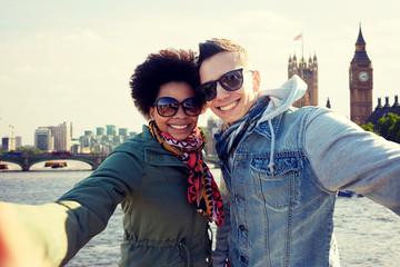 happy teenage couple taking selfie in london city