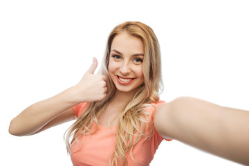 happy woman taking selfie and showing thumbs up