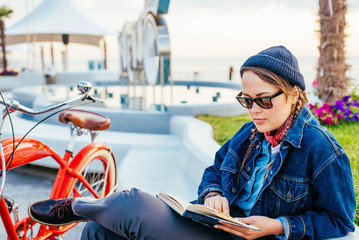 young woman with vintage bicycle resting and reading a book on seaside