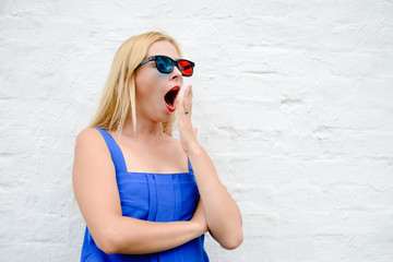 Beautiful blond girl watching scary movie with 3D glasses, hiding exciting holding hands. portrait closeup