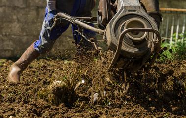 Farmer using machine mart cultivator for ploughing soil