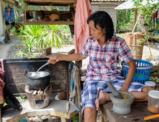 Senior women cooking outdoor, Thai countryside and local lifestyle, mother cooking outdoor sitting in hut with pot and firing firewood in stover