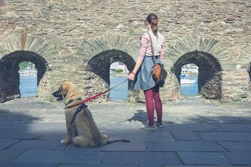 Woman walking dog near stone walls
