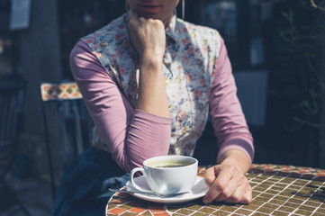 Young woman having coffee outside