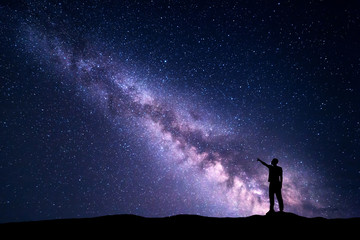 Milky Way with silhouette of a standing young man pointing finger in night starry sky on the mountain. Night landscape. Beautiful Universe, travel background with purple sky full of stars