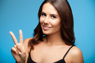 Woman showing two fingers or victory gesture, on blue