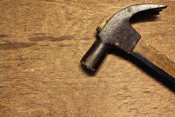 Old rusty hammer and nails on wood table background