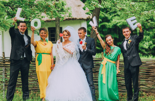 bride and groom with happy groomsmen and bridesmaid holding a letter of tissue shape