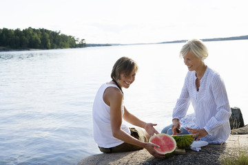 Two women eating watermelon by the sea, Sweden.
