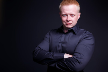 self-confident man smiling with his arms crossed. handsome red-haired businessman in a black shirt on a black background