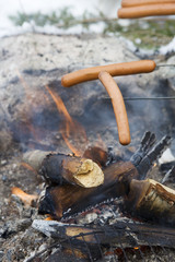 Close-up of sausages grilling over campfire