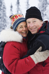 A middle aged couple hugging in the snow, Sweden.