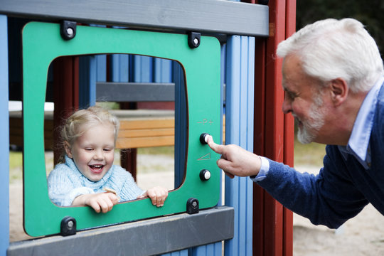 Grandfather and grandchild playing together on a playground, Sweden.