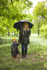 Mother and daughter walking in the rain in a park, Sweden.