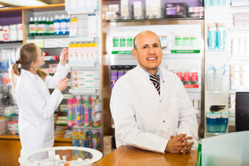 Pharmacist and female assistant helping