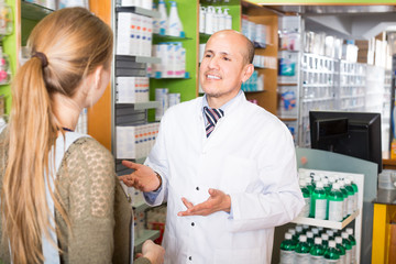 Pharmaceutist helping girl to choose medication