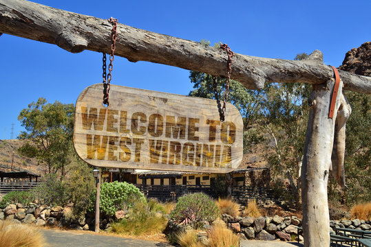 """wood signboard with text """" welcome to west virginia"""" hanging on a branch"""