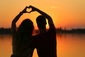 young couple doing heart shape with their hands on lake