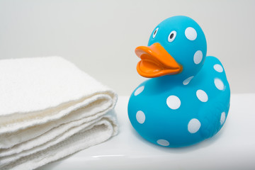 Cute Rubber Duck beside White Towel in Bathroom Close Up