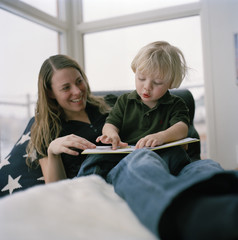 Mother and child reading a book, Sweden.