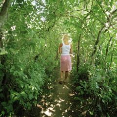A young woman in a lush garden, Sweden.