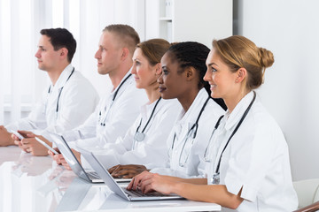 Doctors Using Laptop In Meeting