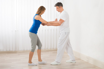 Physiotherapist Assisting Woman For Exercising