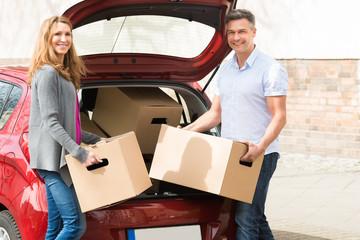 Couple Putting Cardboard Box In Car Trunk