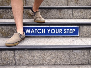 Watch your step sign on a staircase and a pair of feet