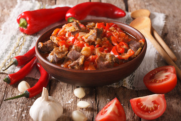 pieces of lamb stewed with onion, tomato and pepper close-up. horizontal