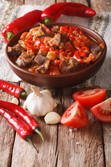 lamb stew with onions, tomatoes and pepper in a bowl close-up. vertical