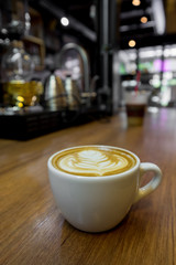 A cup of latte art coffee. Cappuccino coffee on wooden table wit