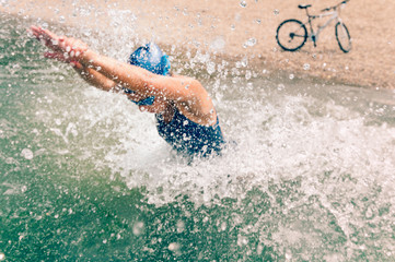 Triathlon. Action shot of a female triathlete starting a swimming stage