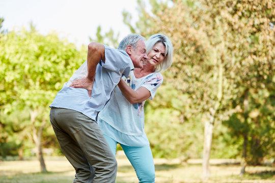 Frau hilft Mann mit Rückenschmerzen im Park