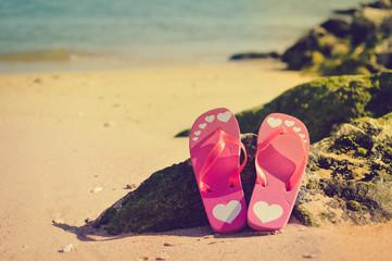 Top view of flip flops left on sandy beach background