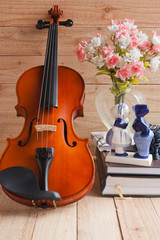 Violin and romantic doll on wood background
