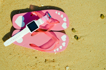 Flipflops and smart watch on sandy ocean beach vacation of concept, top view flat lay style