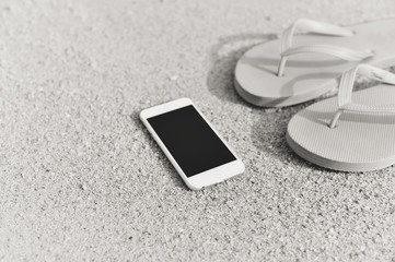 Black white photo on smartphone on the beach background. Top view flat lay style closeup