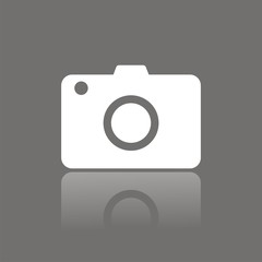 Compact camera icon with reflection on dark background
