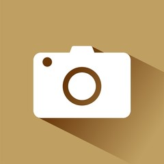 Compact camera icon with shadow on brown background
