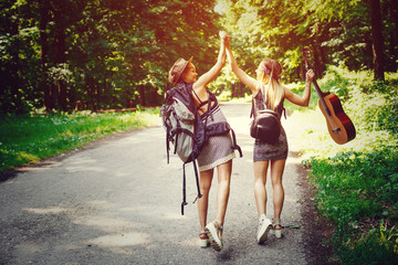 Two woman traveler walking along the road through woods