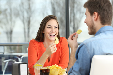 Couple talking and eating chip potatoes