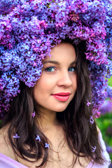 Beautiful young girl in a wreath of lilac.
