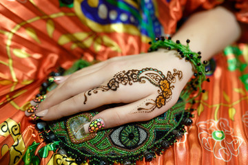 womans hand mehendi picture orange bright fabric with pleats