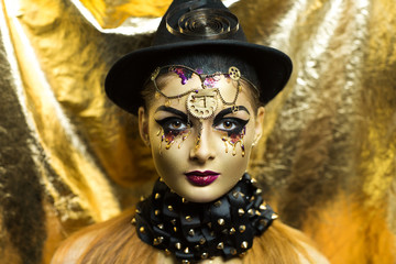 Magic golden girl with bright makeup. Streams of gold, shiny tears drops on the cheeks, black steam punk hat, big collar, body art. Pink lips, chins, decorations, accessories. Professional photo, idea