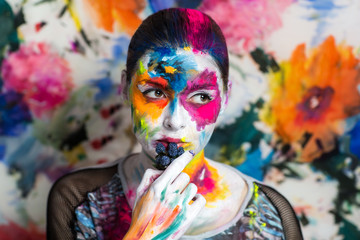 Portrait of beautiful young girl, woman, lady,model,painting, canvas,art, painting,expressionism. Bright creative makeup, expressive eyes, paint, colorful, yellow, blue pink, white flowers. hand berry