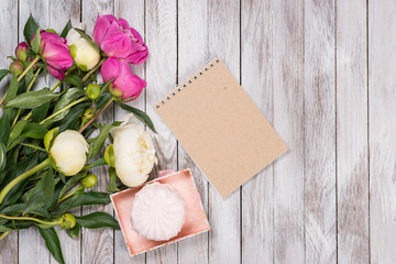 A bouquet of peonies flowers, marshmallow, notebook on white wooden background. Space for text. Top view.