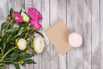 A bouquet of peonies flowers, marshmallow, notebook on the white wooden background. Space for text. Top view.