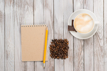 Notebook with a pencil next to coffee and coffee beans, piece of chocolate on white wooden background. Place for text. Top view.
